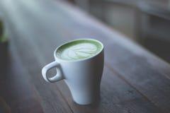 Heiße grüner Tee Lattekunst auf dem Holztisch Stockbilder