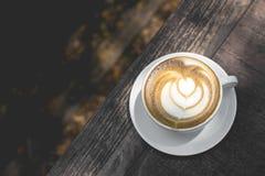Heiße grüner Tee Lattekunst auf dem Holztisch Stockfotografie