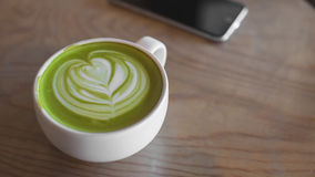 Heiße grüner Tee Lattekunst auf Tabellencaféshop Lizenzfreies Stockbild
