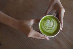 Heiße grüner Tee Lattekunst an Hand auf Tabellencaféshop Lizenzfreie Stockfotos