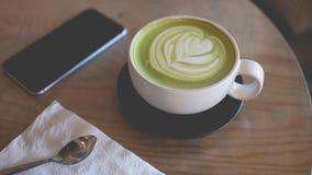 Heiße grüner Tee Lattekunst an Hand auf Tabellencaféshop Stockfotos