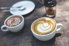 Heiße grüner Tee Lattekunst und heiße Schokolade auf dem hölzernen Stockbild