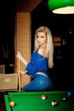 Heiße junge Blondine, die auf dem Billardtisch mit dem Stichwort aufwerfen Lizenzfreies Stockfoto