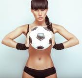 Heiße junge Frau, die ein soccerball anhält stockfotografie
