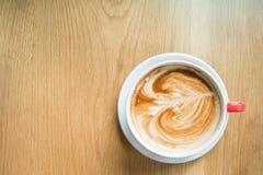 Heiße Kaffee-Kunst auf hölzerner Tabelle Lizenzfreies Stockfoto