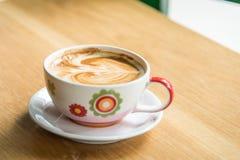 Heiße Kaffee-Kunst auf hölzerner Tabelle Lizenzfreie Stockfotos