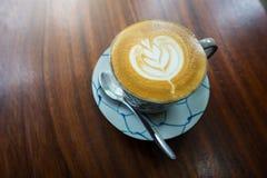 Heiße Kaffee Lattekunst auf hölzerner Tabelle Lizenzfreie Stockfotografie