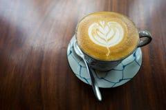 Heiße Kaffee Lattekunst auf hölzerner Tabelle Lizenzfreies Stockbild