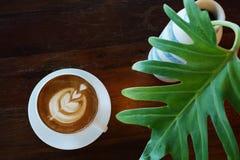 Heiße Kaffee Latteschale auf altem hölzernem Tabellenhintergrund mit tropischem Lizenzfreie Stockfotografie