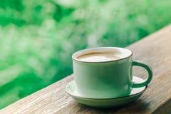 Heiße Kaffeetasse auf natürlichem grünem Hintergrund Stockfotografie