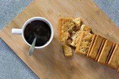 Heiße Kaffeetasse mit Rauche und Cracker auf Holz stockbilder