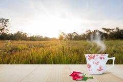 Heiße Kaffeetasse und rote Blume auf die Holztischoberseite auf unscharfem Wiesen- und Waldhintergrund mit weichem Sonnenlicht Lizenzfreies Stockbild