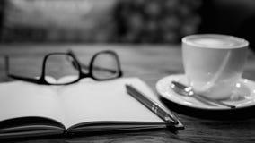 Heiße Lattekunst-Kaffeetasse auf Holztisch und Anmerkungsbuch, Weinlese Lizenzfreie Stockbilder