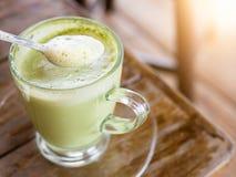 Heiße Milch des grünen Tees im Glasbecher Stockfotografie