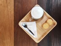 Heiße Milch mit Holz einiger Kekse auf dem Tisch Lizenzfreies Stockfoto