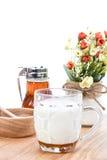 Heiße Milch mit Honig, Honigglas und Honigschöpflöffel auf weißem backgro Stockbilder