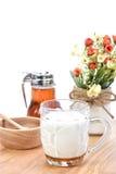 Heiße Milch mit Honig, Honigglas und Honigschöpflöffel auf weißem backgro Stockfoto