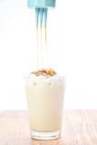 Heiße Milch mit süßer Karamellsoße auf einem weißen Hintergrund Stockbild