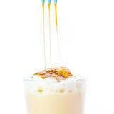 Heiße Milch mit süßer Karamellsoße auf einem weißen Hintergrund Stockfotos
