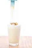 Heiße Milch mit süßer Karamellsoße auf einem weißen Hintergrund Lizenzfreies Stockfoto