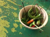 Heiße Paprikas auf der grünen Schmutztabelle Stockfotos