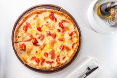 Heiße Pizza Fleisch der Draufsicht mit hamon, Käse- und Kirschtomaten auf dem hölzernen Brett auf der gedienten Restauranttabelle Stockbild