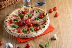 Heiße Pizza mit Prosciutto, Mozzarella, Kirschtomaten und Basilikum, diente auf einem Holztisch für ein Abendessen im italienisch Lizenzfreie Stockbilder