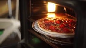 Heiße Pizza wird aus dem Ofen heraus genommen stock video footage
