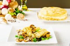Heiße russische Pfannkuchen oder Blini mit Pilzen Stockfotografie