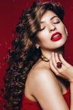 Heiße Schönheit mit den roten Lippen und den Blumenblättern Stockfoto