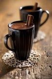 Heiße Schokolade in den schwarzen Bechern mit Zimtsteuerknüppel lizenzfreie stockfotos