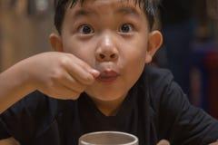 Heiße Schokolade des jungen asiatischen Jungengetränks Stockfotos