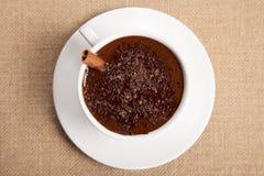 Heiße Schokolade im weißen Becher mit Zimtsteuerknüppel Stockfoto