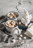 Heiße Schokolade mit Eibischen, keramischer Santa Claus, altem Buch und Handschuhen Stockbild