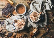 Heiße Schokolade mit Schlagsahne, Zimt, Nüssen und Kakaopulver lizenzfreie stockbilder