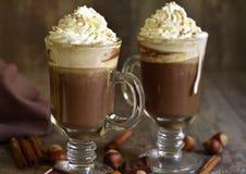 Heiße Schokolade mit Zimt und Haselnüssen in einem Glas stockbilder