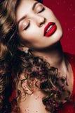 Heiße sinnliche Frau mit den roten Lippen und den rosa Blumenblättern Stockfotografie