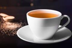Heiße Tee-Schale und Cane Sugar Spritzen auf dunklem oder schwarzem Hintergrund Stockfoto