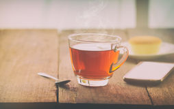 Heiße Teeschale mit Butterkuchen und smartpho auf dem Tisch auf den wi Lizenzfreie Stockfotografie