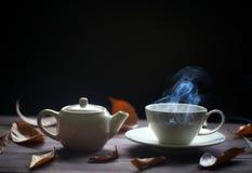 Heiße Teeschale und Teekanne auf hölzernem Hintergrund mit Dampf lizenzfreies stockfoto