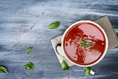 Heiße Tomatensuppe mit Basilikumblättern Lizenzfreie Stockbilder