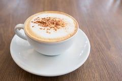 Heißer Cappuccino auf Holztisch Stockbilder