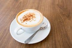 Heißer Cappuccino auf Holztisch Lizenzfreie Stockfotografie