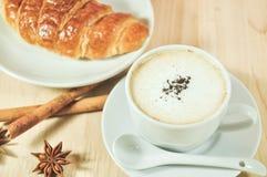 Heißer Cappuccino und Hörnchen mit Zimt, Anis auf hölzerner Tabelle Stockfotografie