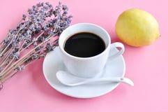 Heißer Espresso und Lavendel blühen mit Zitrone auf rosa hölzerner Tabelle Lizenzfreie Stockbilder
