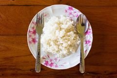 Heißer gedämpfter Reis diente auf einem Teller von Blumen stockfotos