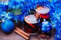 Heißer Glühwein mit Gewürzen und blauer Girlande Lizenzfreies Stockfoto