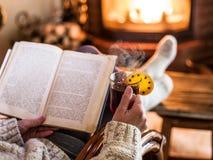Heißer Glühwein und Buch in den Frauenhänden Lizenzfreies Stockfoto