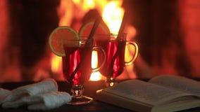 Heißer Glühwein und ein Buch auf dem Tisch Kamin mit Feuer auf dem Hintergrund stock footage