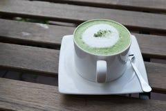 Heißer grüner Tee auf hölzerner Tabelle Stockbild